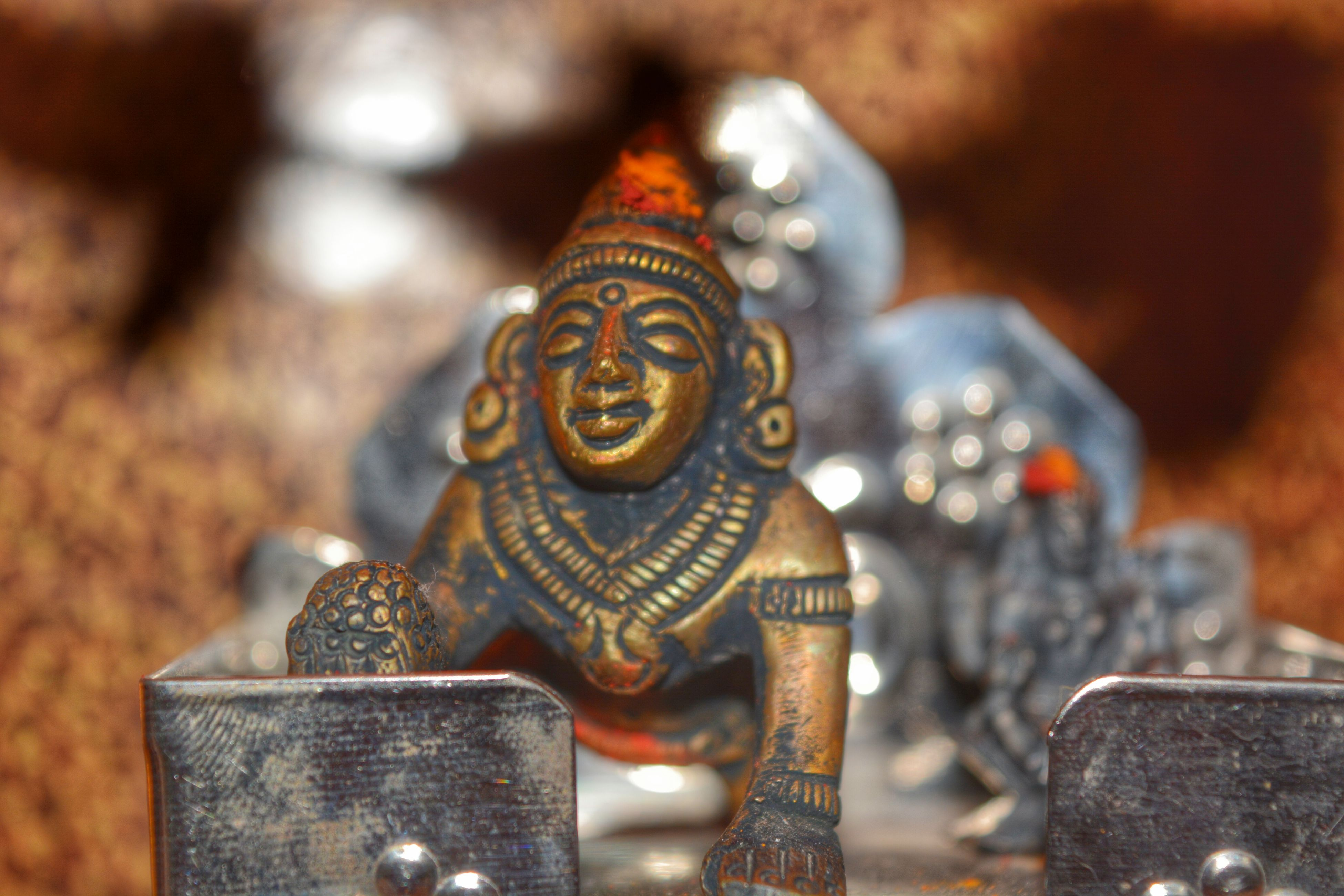 focus on foreground, close-up, art and craft, gold colored, statue, art, sculpture, religion, human representation, creativity, carving - craft product, spirituality, temple - building, ornate, selective focus, animal representation, history, buddha