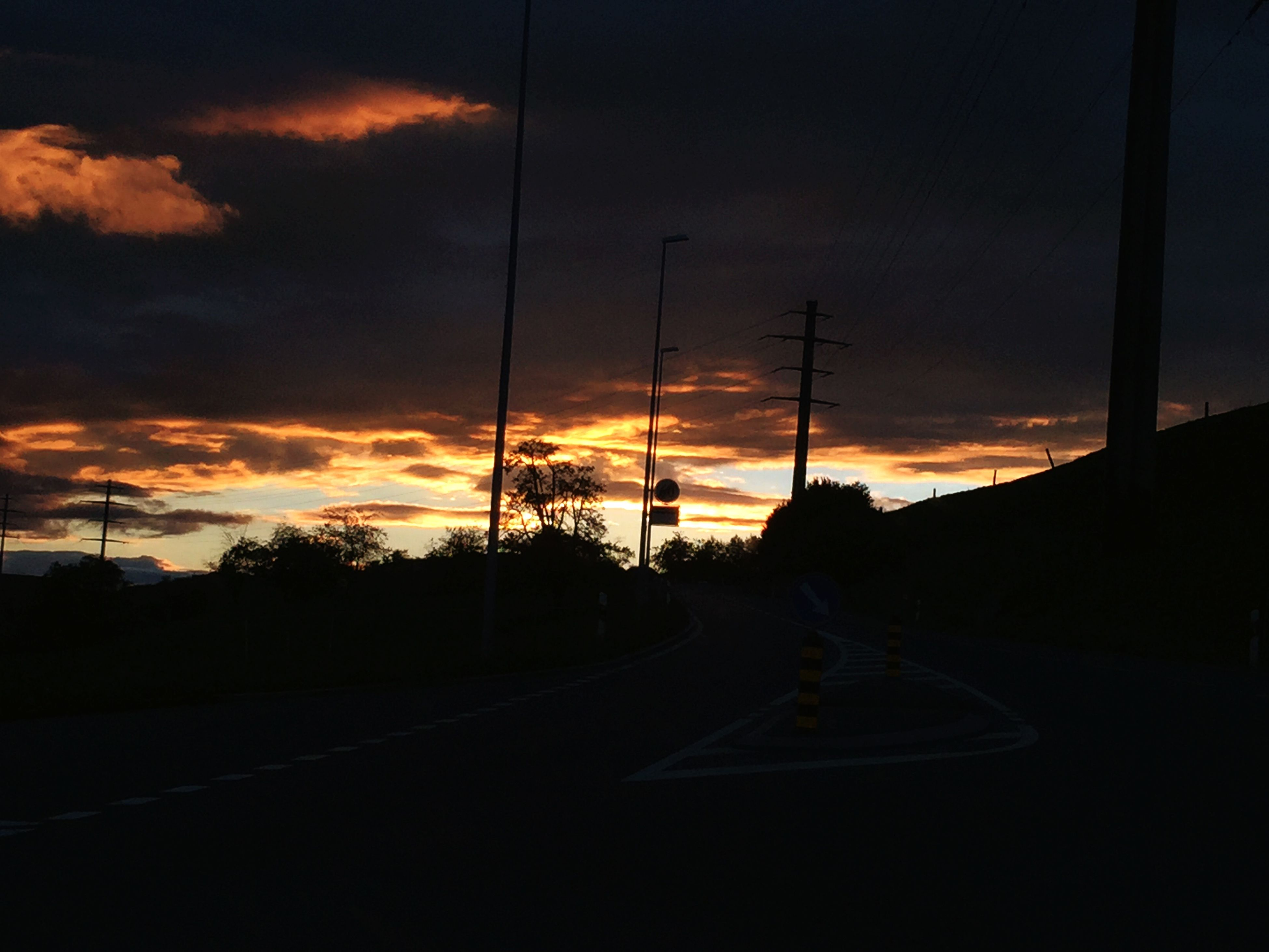 sunset, transportation, sky, silhouette, road, cloud - sky, car, the way forward, orange color, mode of transport, land vehicle, street, cloud, street light, dark, diminishing perspective, beauty in nature, nature, dusk, scenics
