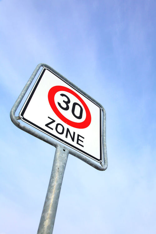 German speed limit sign 30 City Limits Communication Concept Copy Space German Germany Kilometer Low Angle View Maximum Metal No People Number Outdoors Pole Road Sign Sign Sky Slow Speed Speed Limit Sign Text Thirty Traffic Sign Warning Sign