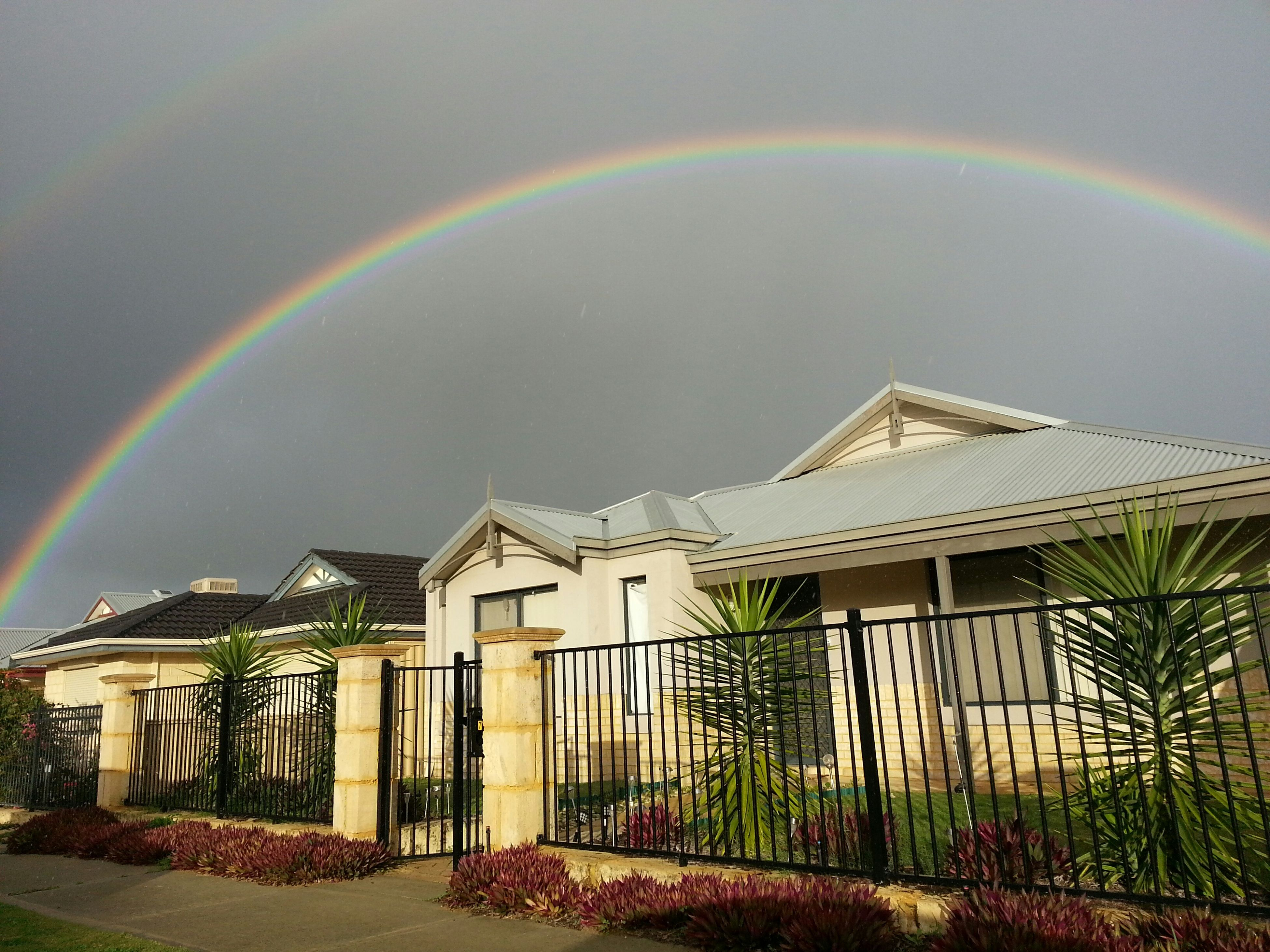 architecture, built structure, building exterior, house, sky, rainbow, residential structure, residential building, railing, multi colored, cloud - sky, outdoors, fence, no people, nature, day, building, plant, roof, cloud