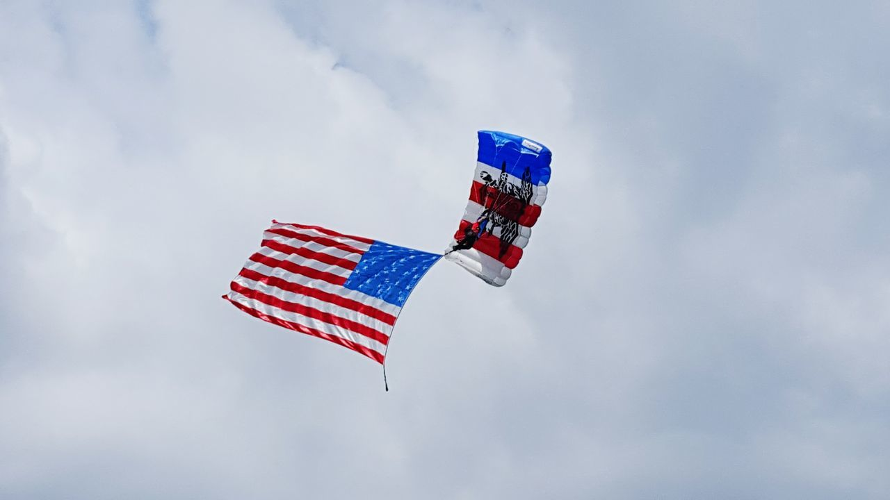 Paratrooper performing in the sky at the Lincoln Financial Center. Paratrooper Parachute Flag American Flag Redwhiteandblue Sky Performance Event at the Eagle training camp day.