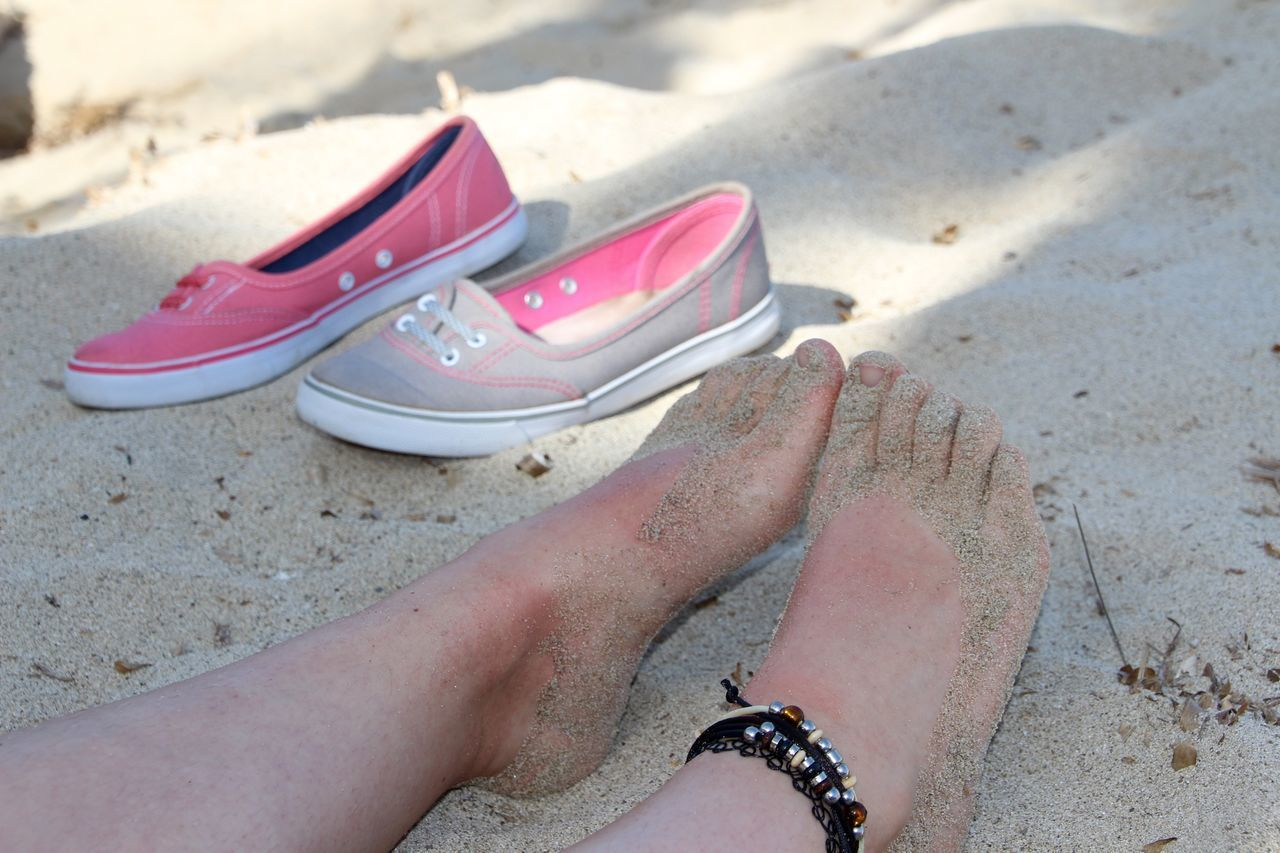 Low Section Of Messy Legs By Pink Shoes At Beach