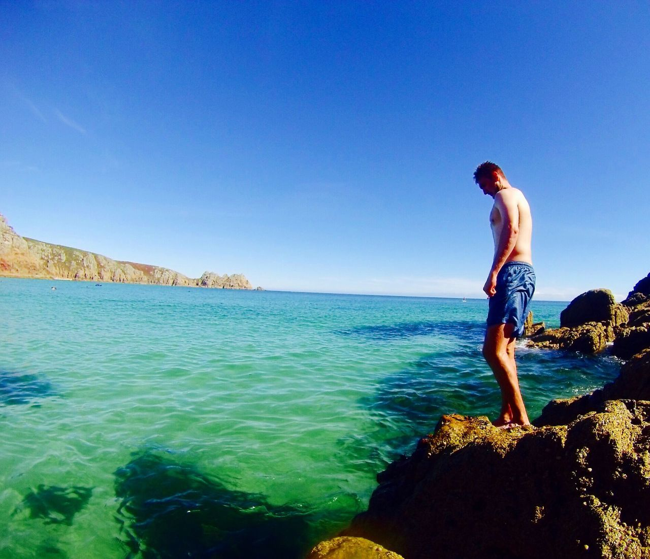 water, real people, sea, rock - object, one person, full length, leisure activity, standing, lifestyles, clear sky, nature, shirtless, day, blue, scenics, beauty in nature, horizon over water, outdoors, rear view, tranquil scene, sunlight, men, tranquility, sky, young adult, adult, people