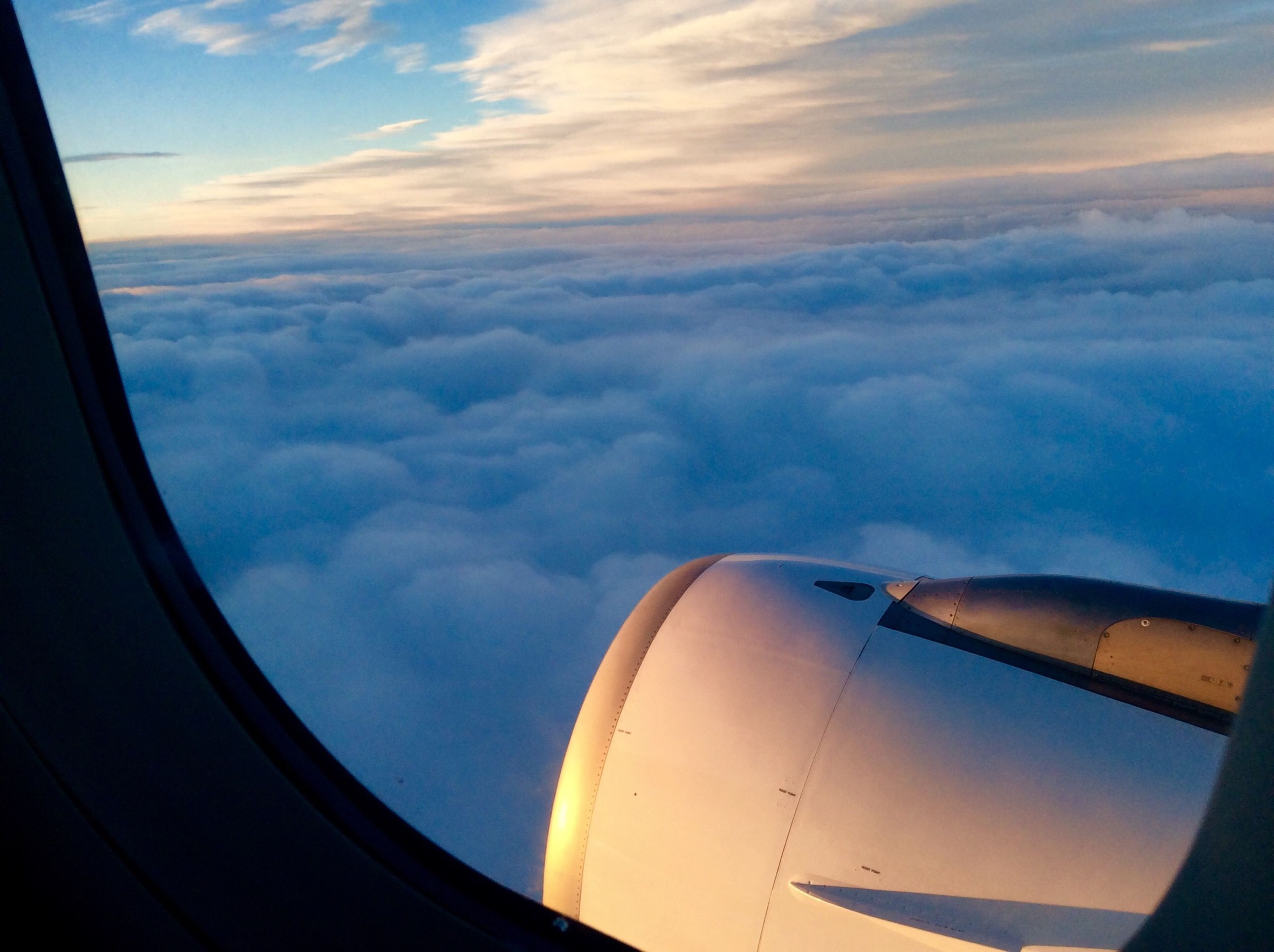 transportation, airplane, air vehicle, mode of transport, sky, part of, cloud - sky, cropped, aircraft wing, flying, cloud, public transportation, travel, journey, on the move, mid-air, aerial view, no people, vehicle part, glass - material