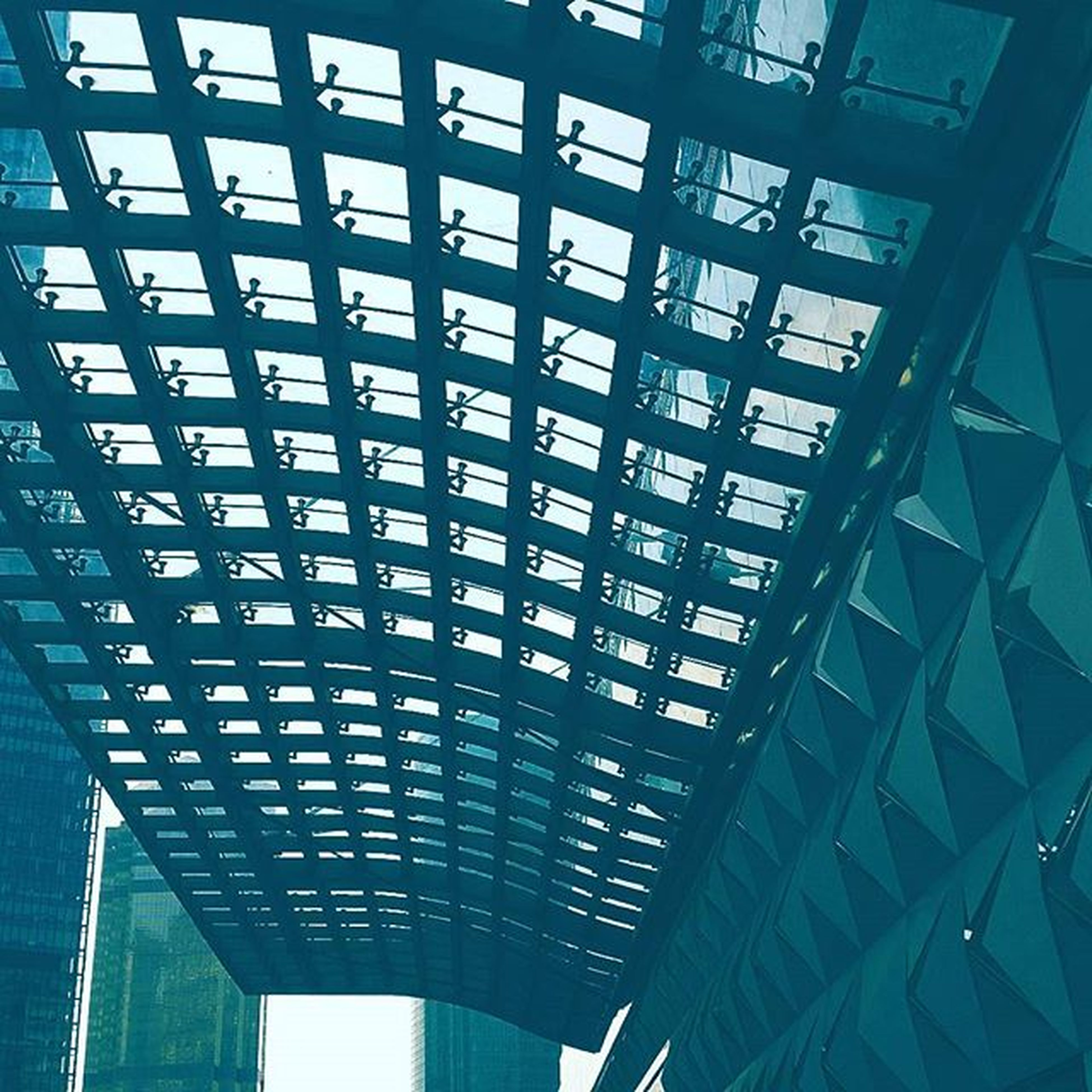 architecture, built structure, low angle view, indoors, ceiling, modern, pattern, architectural feature, glass - material, metal, no people, blue, day, grid, sky, connection, repetition, building exterior, sunlight, design