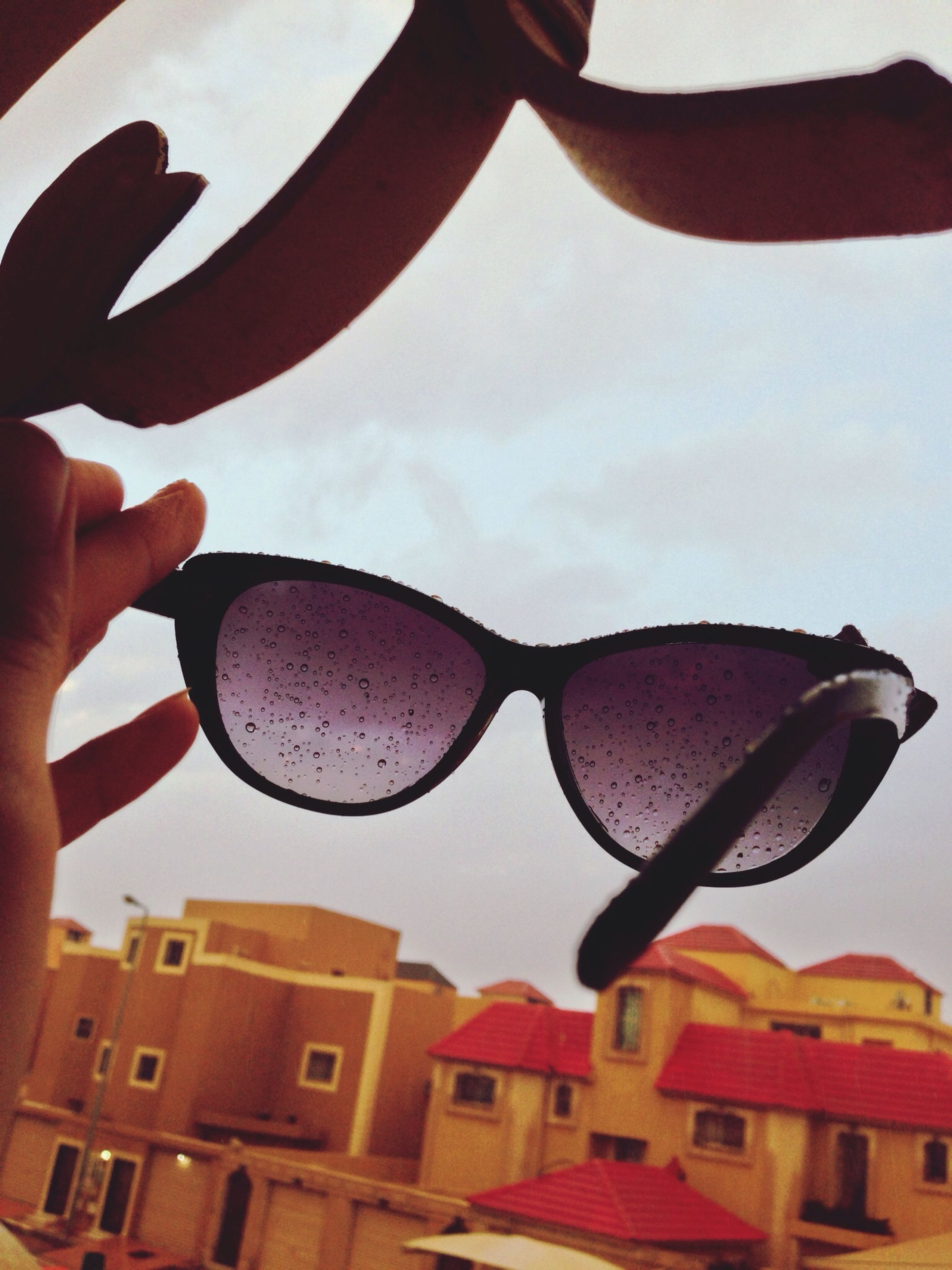 built structure, building exterior, architecture, leisure activity, part of, lifestyles, person, cropped, holding, sky, sunglasses, day, unrecognizable person, outdoors, city, close-up, reflection