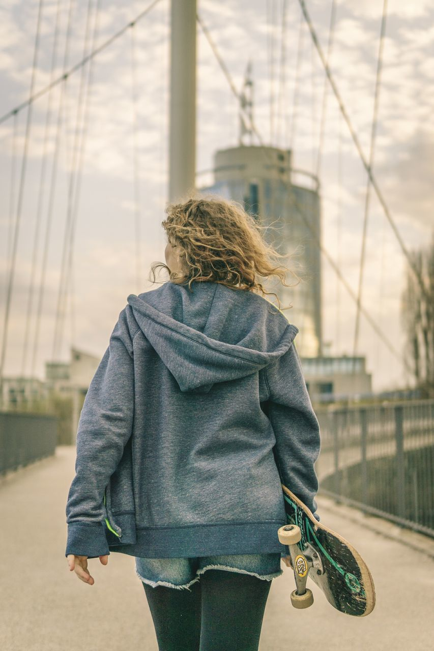 rear view, architecture, built structure, walking, bridge - man made structure, one person, transportation, real people, day, young adult, outdoors, focus on foreground, lifestyles, young women, building exterior, road, women, blond hair, city, sky, people