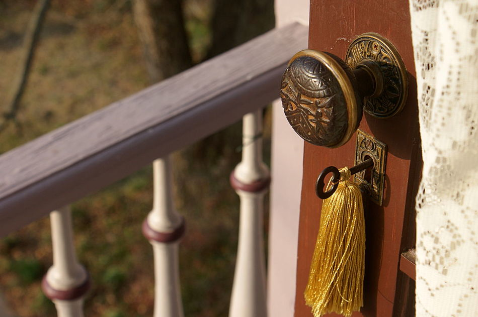 An old antique metal doorknob and vintage key with a gold tassel, leads outside, past lace curtains, to a railed balcony. Balcony Country Life Door Doorknob Doorway Going Out Gold Home Key Lace Curtain Looking Out Open Door Small Town Small Town America View Outside Vintage