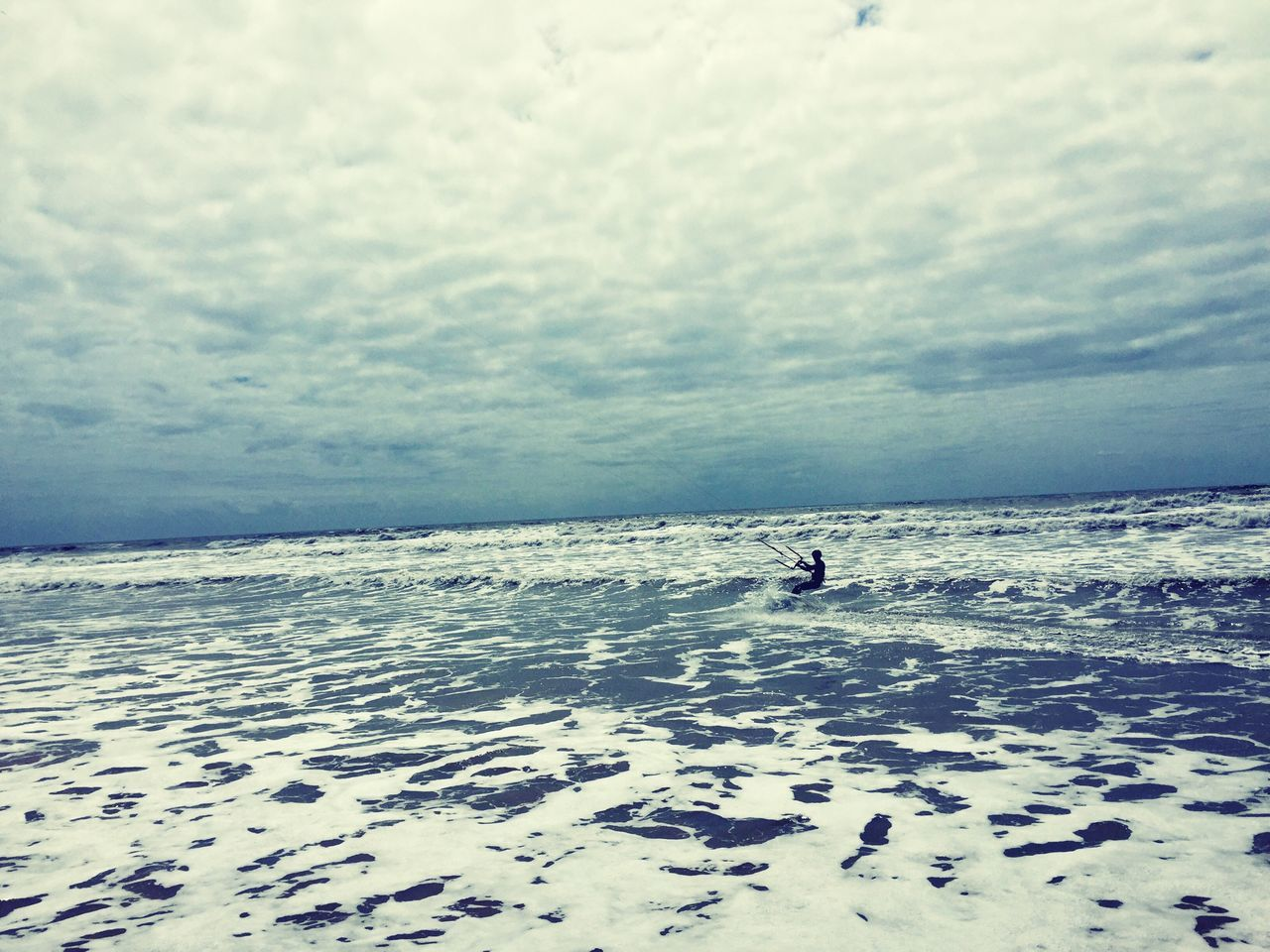 Man Kite Surfing In Sea Against Cloudy Sky