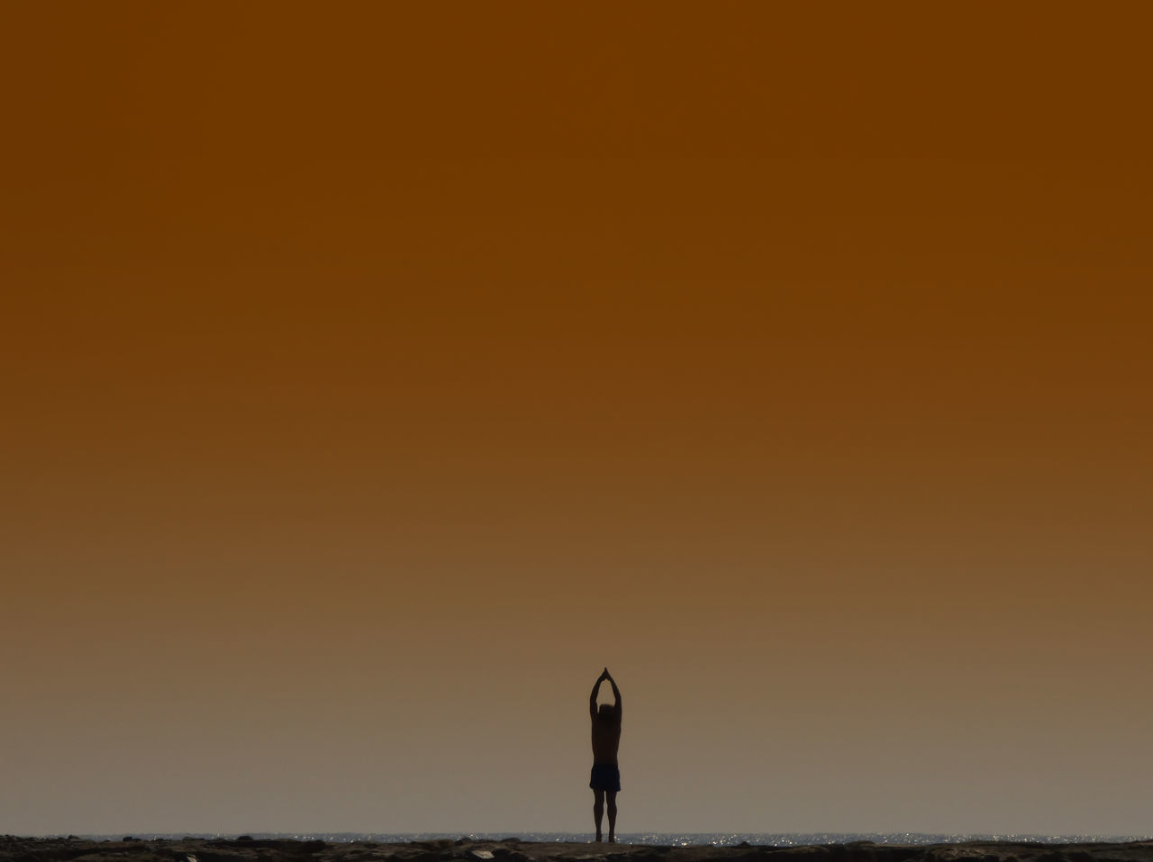 sunset, silhouette, real people, nature, one person, lifestyles, beauty in nature, leisure activity, standing, sea, copy space, outdoors, tranquil scene, scenics, women, tranquility, men, water, sky, horizon over water, full length, clear sky, adult, day, adults only, people