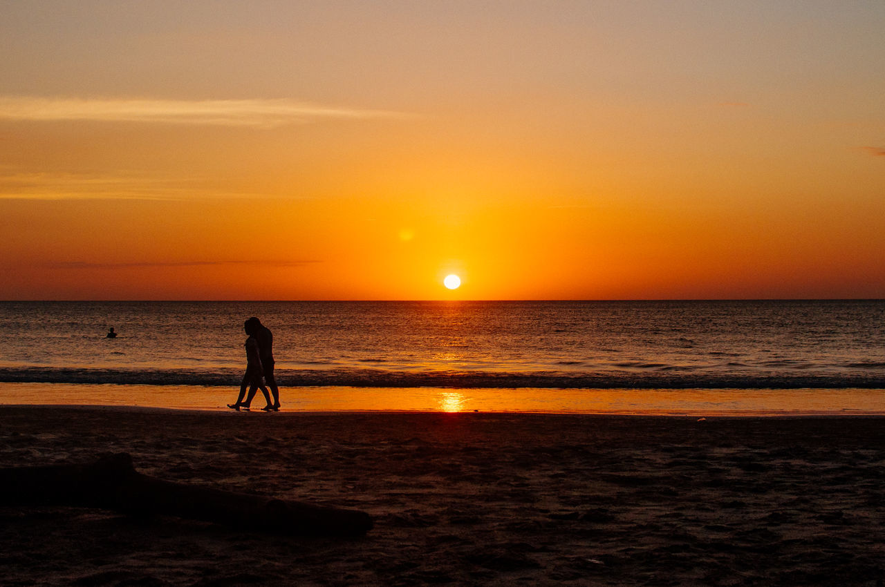 Silhouette Couple Walking At Seashore Against Sky During Sunset