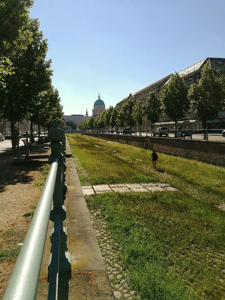 Leerer Stadtkanal in Potsdam_city Part Of Havelland Germany Canal Dutch Canals Empty Clear Sky Potsdam Havel Built Structure by King Of Prussia Grass Tree Footpath Sunlight Day Outdoors Blue Spraying Lawn Diminishing Perspective The Way Forward Green Color Long Tranquility