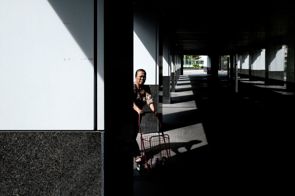 One Person Shadow One Woman Only Day Light And Shadow Pillars Market Trolley Pushing Cart Shopping Walking Street Photography Streetphotography Streetphoto_color Streetlife Street Life Everybodystreet FUJIFILM X-T1