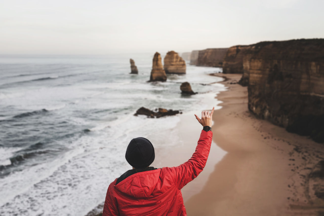 Beach Beauty In Nature Casual Clothing Hand Holding Idyllic Leisure Activity Lifestyles Majestic Men Non-urban Scene Rear View Rock - Object Scenics Sea Tourism Tourist Tranquil Scene Tranquility Travel Destinations Vacations Waist Up Water Wrist Wristwatch