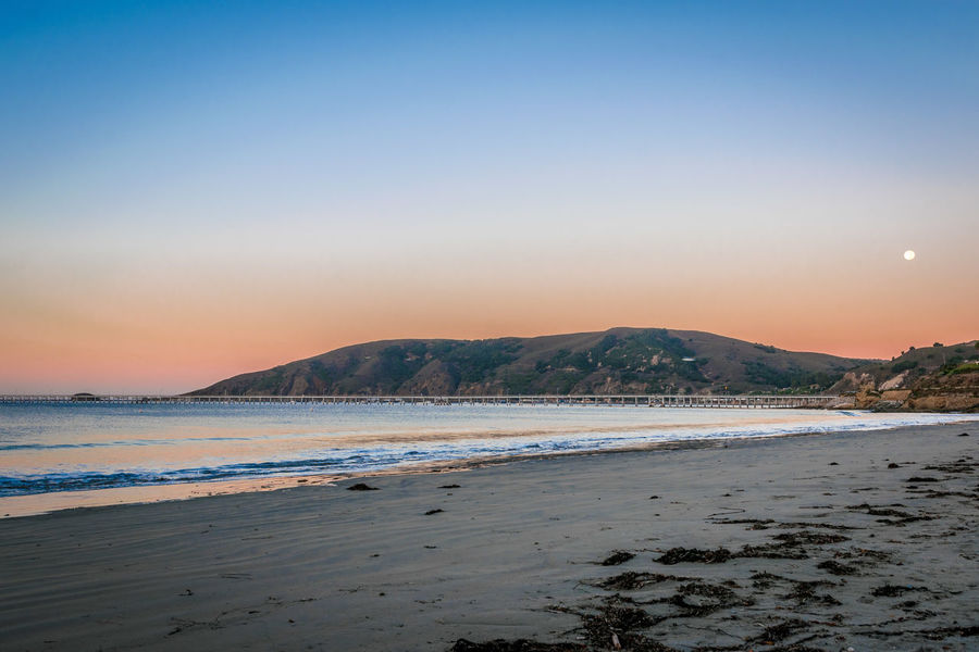 Avila Beach CA Moon Pier Beach Beauty In Nature Clear Sky Mountain Nature Outdoors Sand Scenics Sea Shore Sky Sunrise Sunset Tranquil Scene Tranquility Water Wave