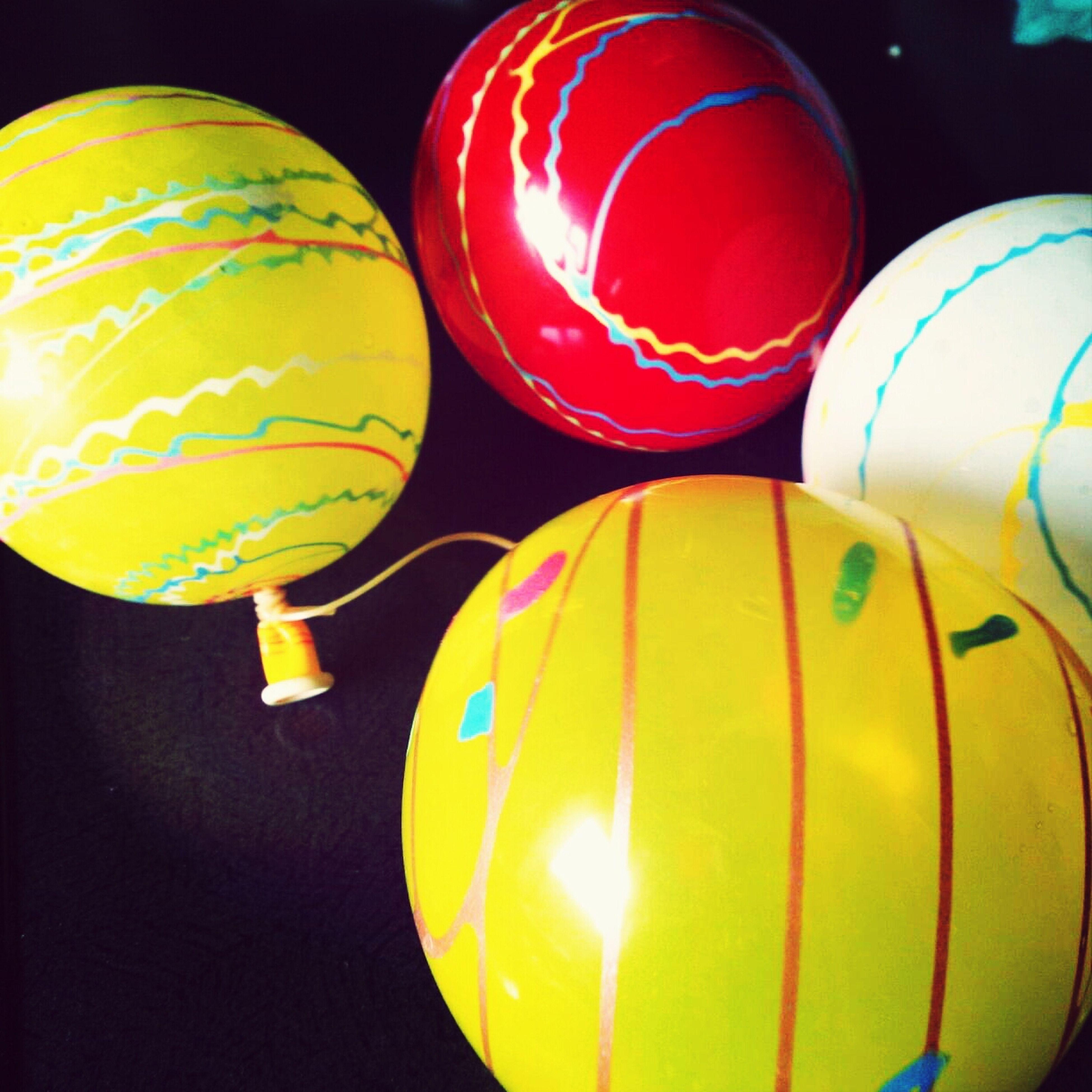 illuminated, low angle view, hot air balloon, multi colored, lighting equipment, circle, decoration, sphere, lantern, balloon, yellow, indoors, close-up, celebration, geometric shape, pattern, hanging, night, no people, shape