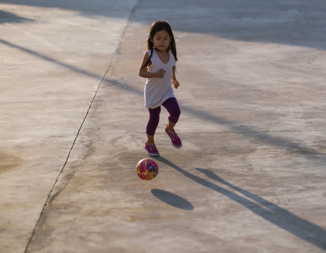 Activity Ball Casual Clothing Child Childhood Children Only City Life Concrete Floor Day Full Length Girl Happiness Leisure Activity Leisure Games One Boy Only One Person Outdoor Pursuit Outdoors People Playing Soccer Speed