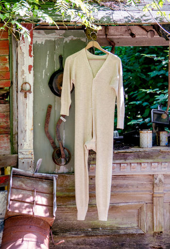 old wool long johns hang from a wood beam in a salvage yard Fun Junk Yard Close-up Cloth Clothing Coathanger Day Drying Grey Growth Hanging Long Johns No People One Person Outdoors Underware Wool