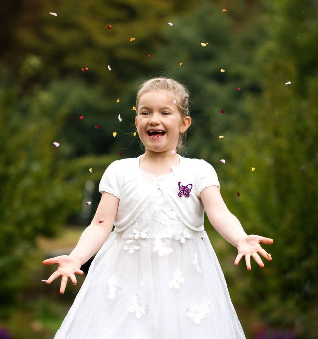 A young bridesmaid in a white dress throwing confetti high in the air and laughing whilst having fun. Bridesmaid Bridesmaids Bridesmaid Dress Flower Girl Confetti Confettis Wedding Wedding Photography Weddings Around The World Wedding Day Weddings Celebration Child Children Only Innocence Smiling Laughing Laughing Smiling :) Fun Funny One Girl Only Happiness Outdoors Throwing