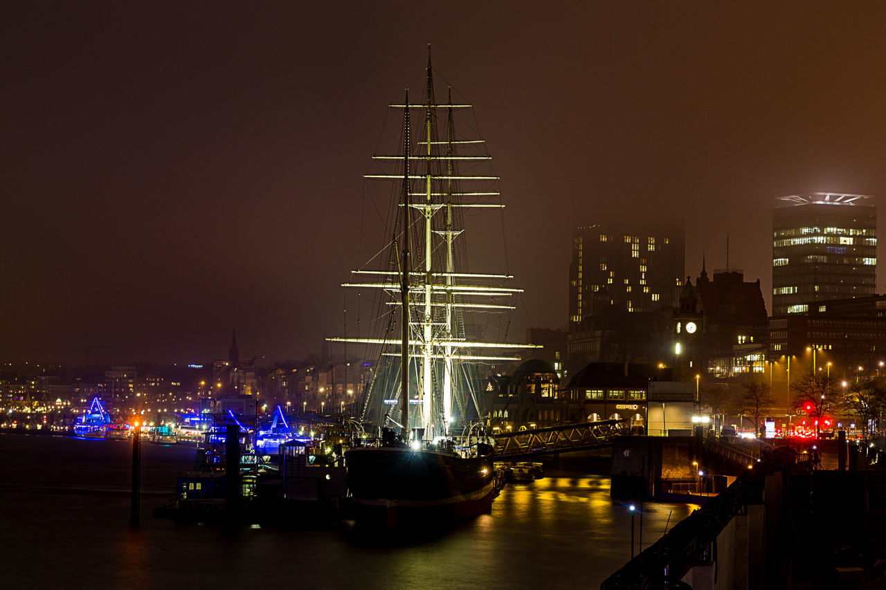 Illuminated Sailing Ship In Sea At Harbor Against Sky