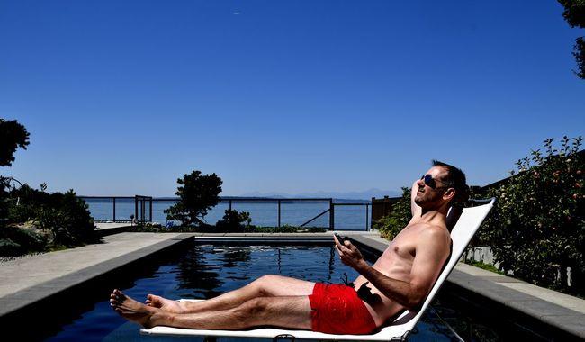 Man Sunbathing Poolside Phone