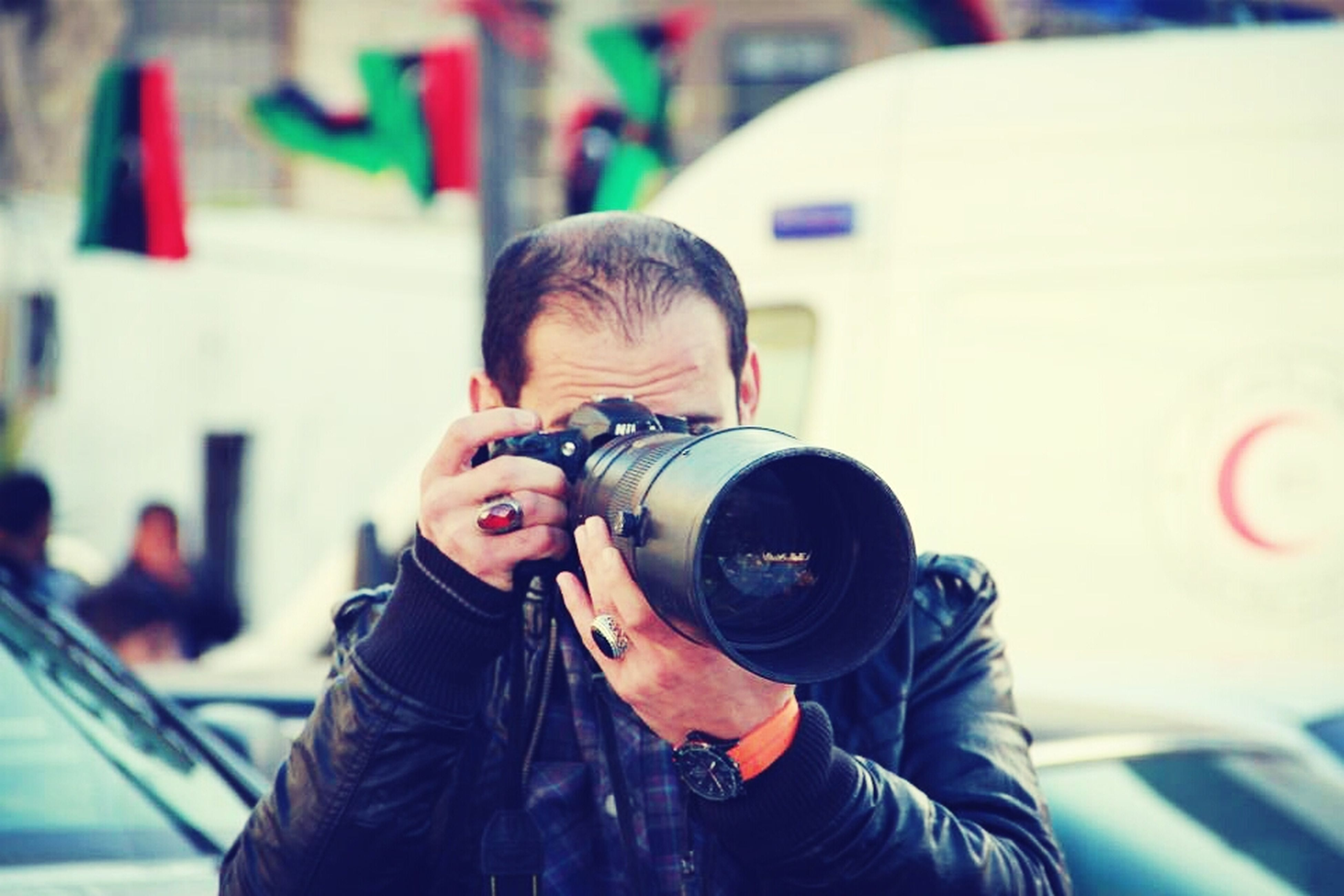 lifestyles, focus on foreground, leisure activity, wireless technology, waist up, photographing, technology, person, photography themes, holding, headshot, communication, smart phone, casual clothing, mobile phone, young adult, head and shoulders, camera - photographic equipment