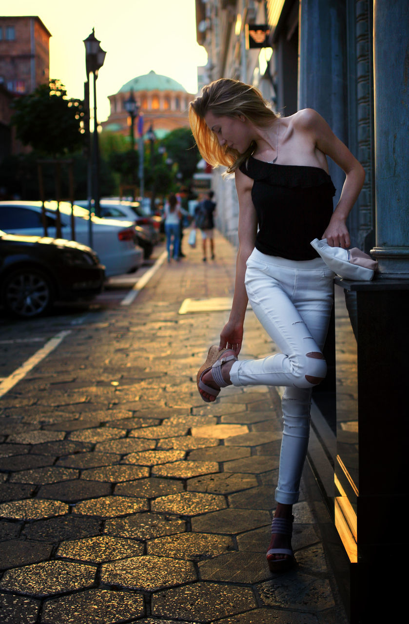 Young Woman Touching Shoe On Sidewalk In City