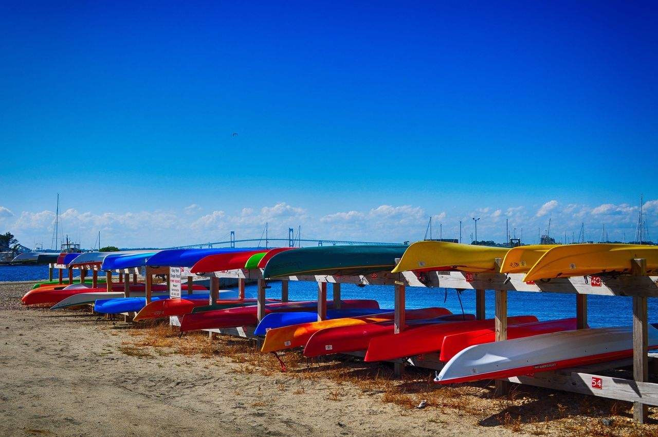 in a row, beach, sand, multi colored, blue, nature, sky, day, shore, copy space, outdoors, no people, sea, tranquility, tranquil scene, scenics, sunlight, large group of objects, beauty in nature, clear sky, pedal boat, moored, summer, travel destinations, vacations, horizon over water, landscape, nautical vessel