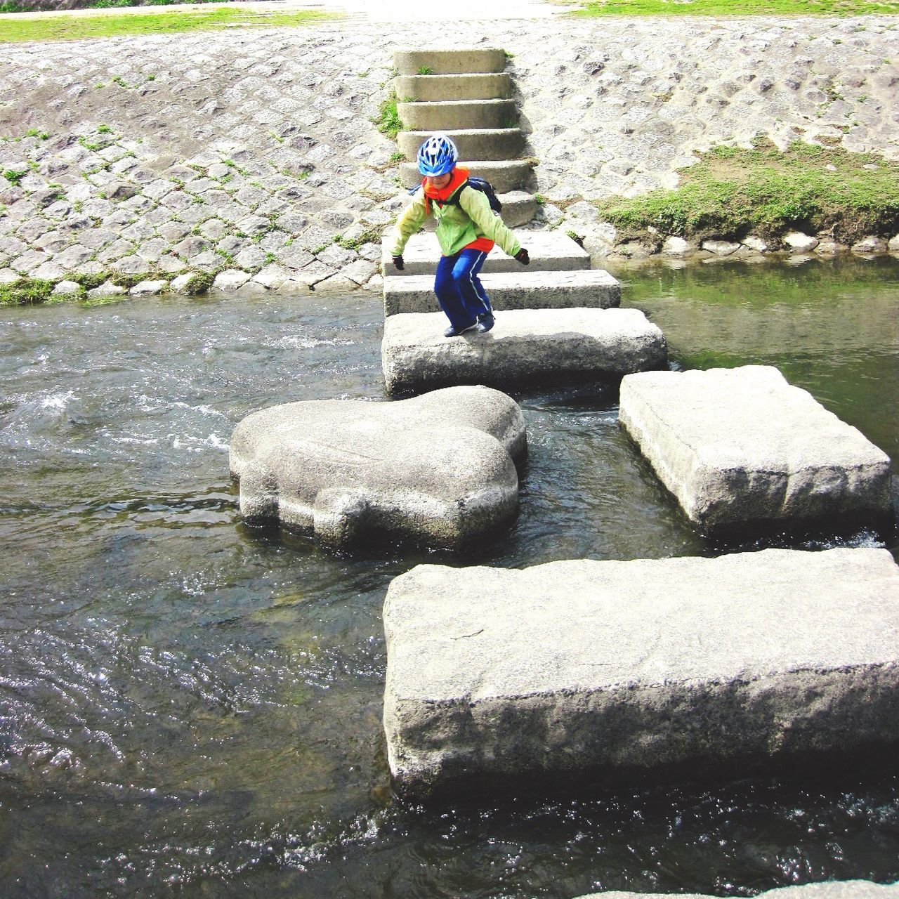 Boy Playing Over Concrete Stones Over River