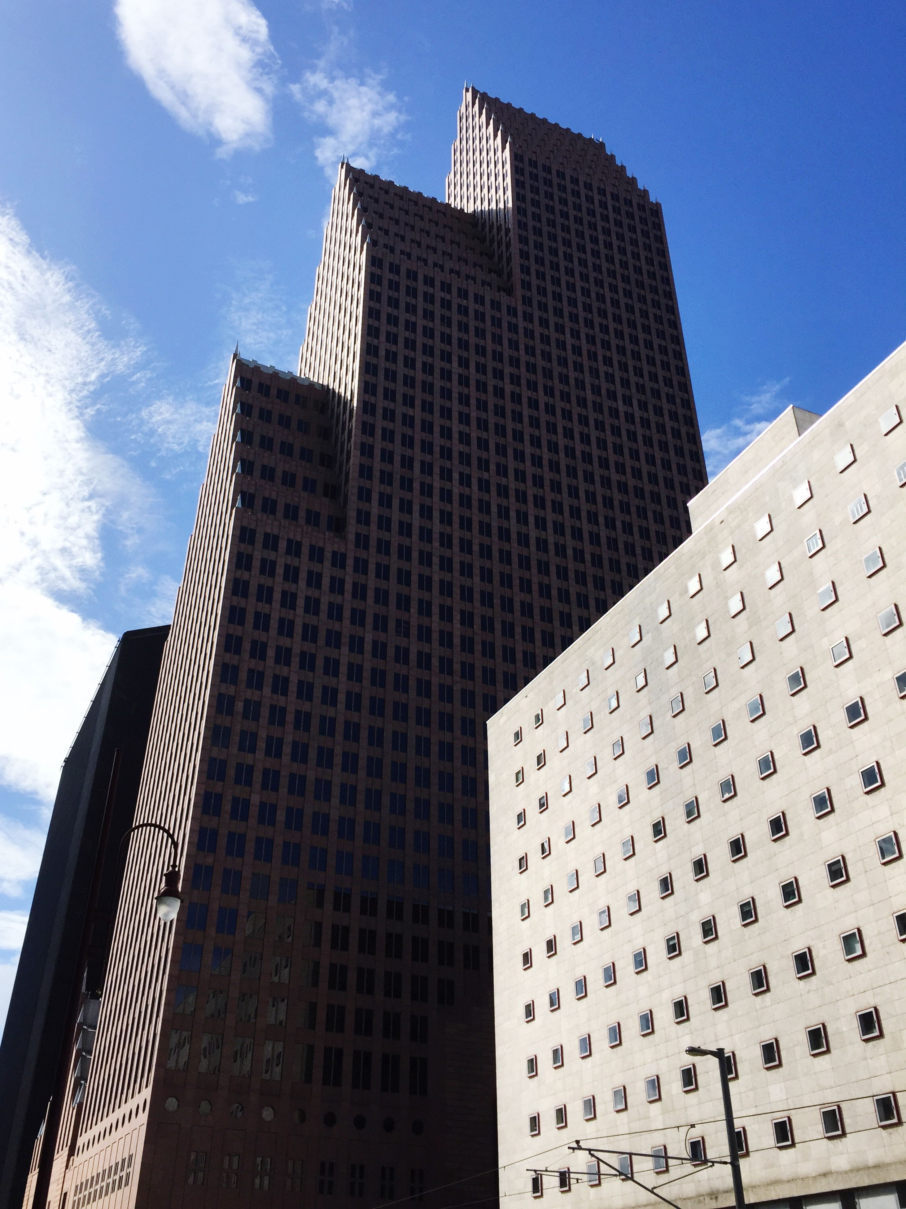 building exterior, architecture, built structure, skyscraper, city, modern, tall - high, office building, low angle view, tower, sky, building, day, blue, tall, outdoors, no people, city life, repetition, cloud - sky, cloud, development, sunny
