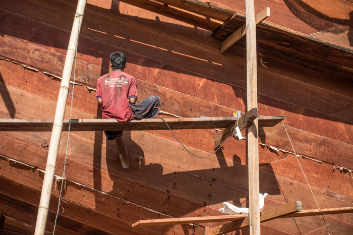 Workers constructing a wooden ship in Indonesia Construction Craftsmen Crazy Hammarby Sjöstad Plank Plant Ship Ship Building Water Wooden Ship