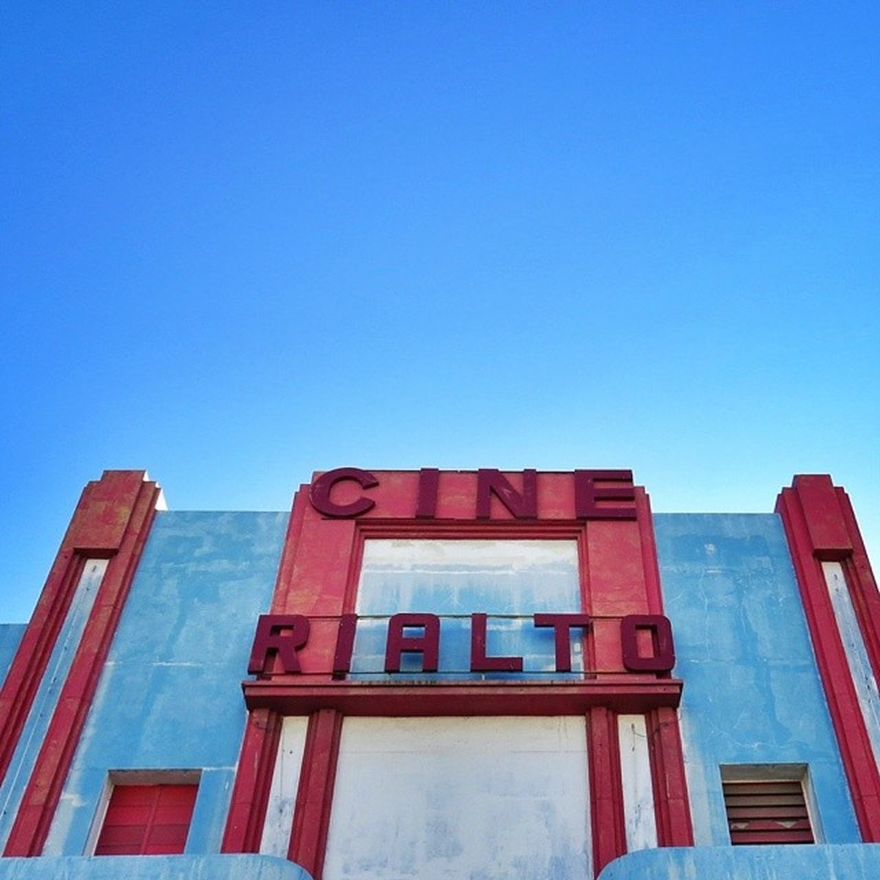 building exterior, blue, architecture, low angle view, built structure, copy space, day, clear sky, no people, red, outdoors, sky