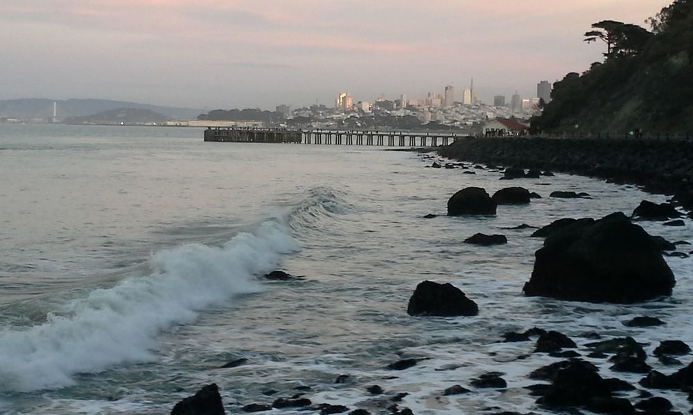 A lovely rocky shoreline at twilight shows grays, soft colors, rocks in shadow and waves, with a pier and part of the city skyline of San Francisco in the background. Bay Bay Area Beach Calm Water City City Scapes Cityscape Coast Coastline Evening Gray Light And Shadow Nature Pier Rocks Sea Shadows Shore Sky Soft Colors  Fine Art Photography Twilight Twilight Sky Water Waves