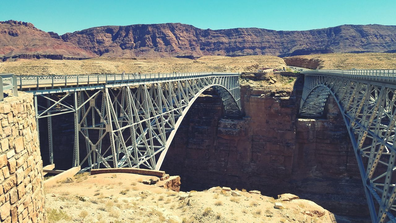 bridge - man made structure, connection, engineering, hydroelectric power, built structure, architecture, dam, arch, arch bridge, day, mountain, outdoors, no people, transportation, sunlight, mountain range, nature, clear sky, sky, water