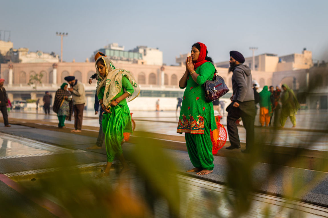 Woman in a green Sari praying before entering the Golden Temple in Amritsar, India Amritsar Famous Place Front View Golden Golden Temple Gurudwara India Indian Pray Praying Punjab Punjabi Religion Sari Sikh Sikh Temple Sikhism Temple Togetherness Tourism Travel Destinations Woman Worship