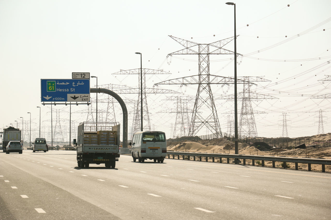 Desert Highway Day Desert Dubai Electricity  Electricity Pylon Heat Heat - Temperature Highway Motion No People Outdoors Street Transmission Line Tower Transmission Tower Transportation Transportation Trucks Vehicle