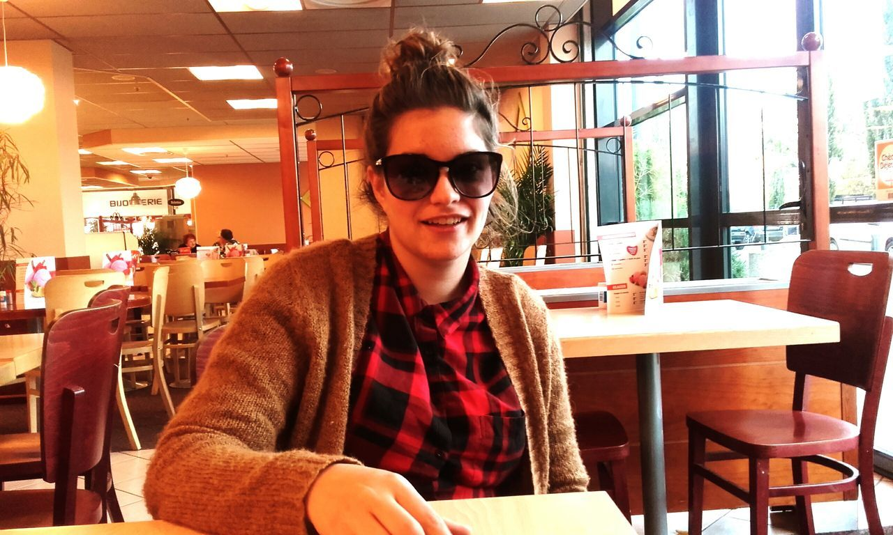 restaurant, cafe, sunglasses, young adult, smiling, sitting, one person, real people, table, young women, happiness, leisure activity, casual clothing, looking at camera, chair, portrait, young men, lifestyles, indoors, cheerful, day, people