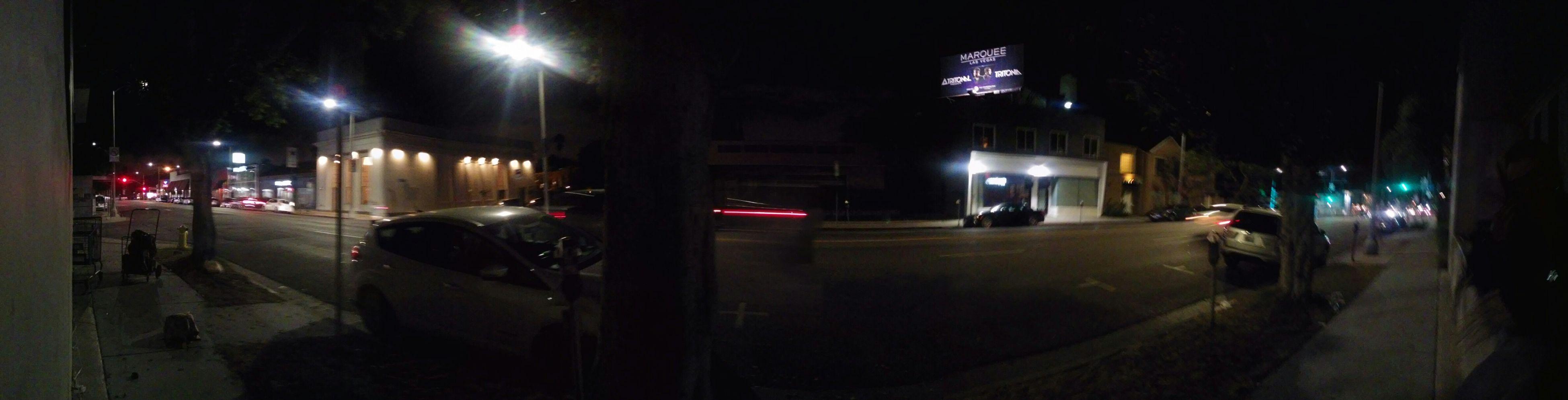 night, illuminated, transportation, land vehicle, car, street, street light, mode of transport, building exterior, road, city, architecture, built structure, city street, lighting equipment, traffic, dark, city life, on the move, headlight