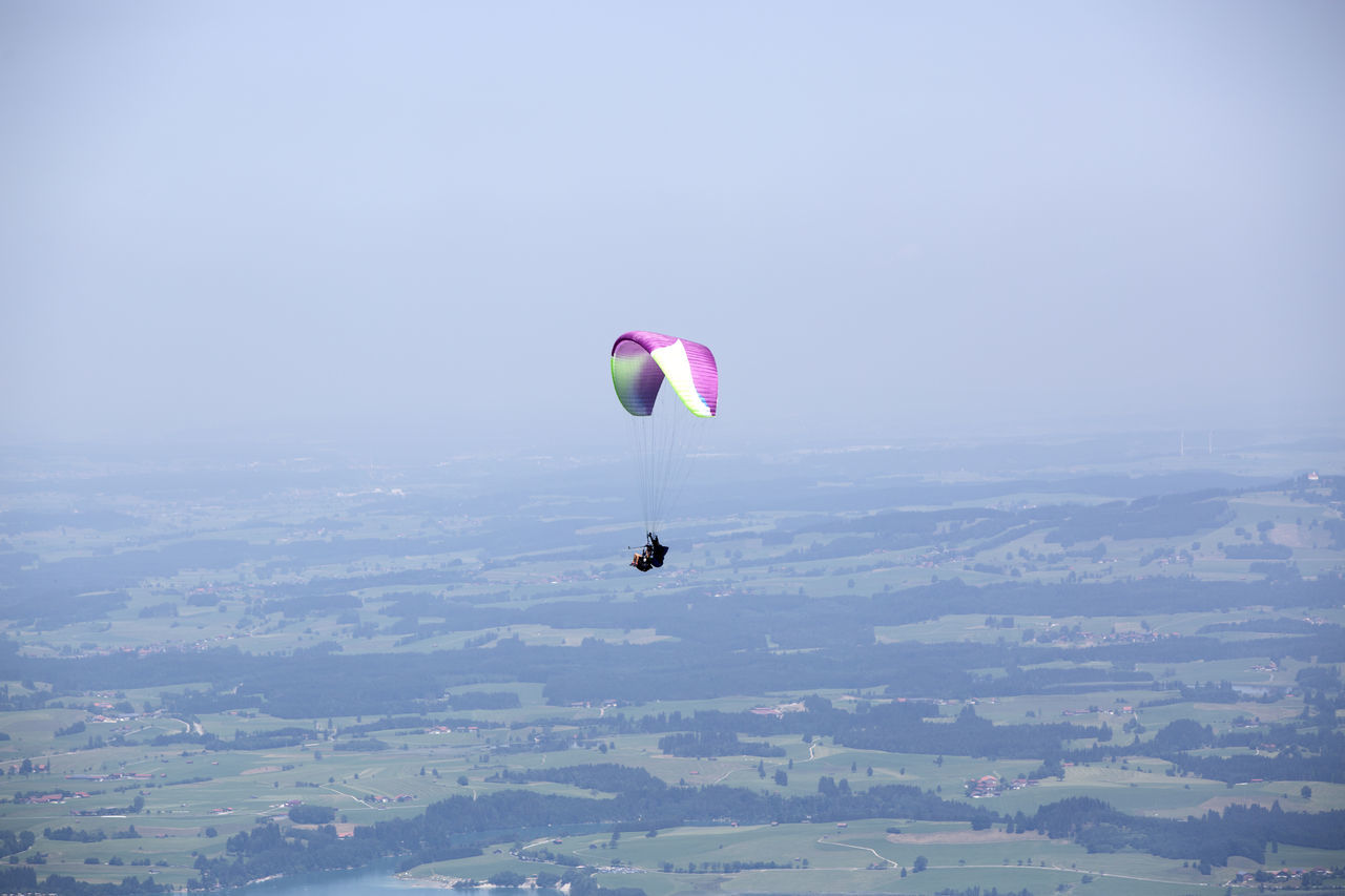 mid-air, adventure, flying, parachute, pink color, sky, clear sky, outdoors, extreme sports, nature, beauty in nature, landscape, scenics, day, multi colored, skydiving, one person, paragliding, hot air balloon, people