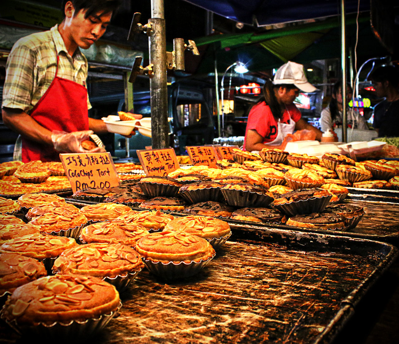 food and drink, food, for sale, freshness, retail, real people, market stall, market, men, small business, baked, choice, outdoors, occupation, sweet food, women, bakery, night, ready-to-eat, one person, people