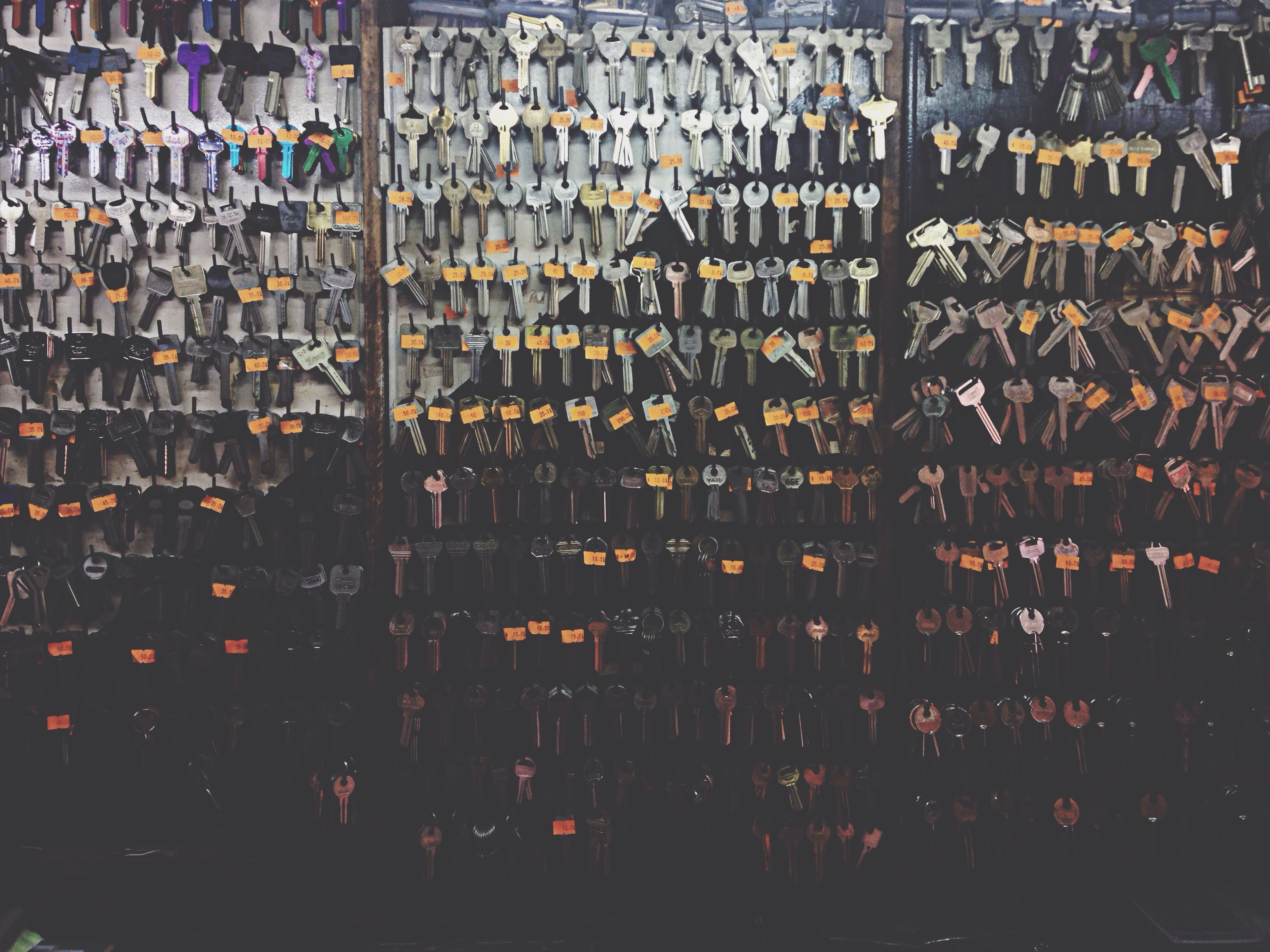 indoors, large group of objects, abundance, full frame, backgrounds, in a row, order, arrangement, pattern, variation, metal, side by side, repetition, hanging, high angle view, no people, store, retail, collection, metallic