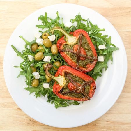 Stuffed red pepper with rocket salad leaves Red Pepper Stuffed Rocket Leaves Salad Olives Feta Cheese Anchovies Savoury Mediterranean Food Pesto
