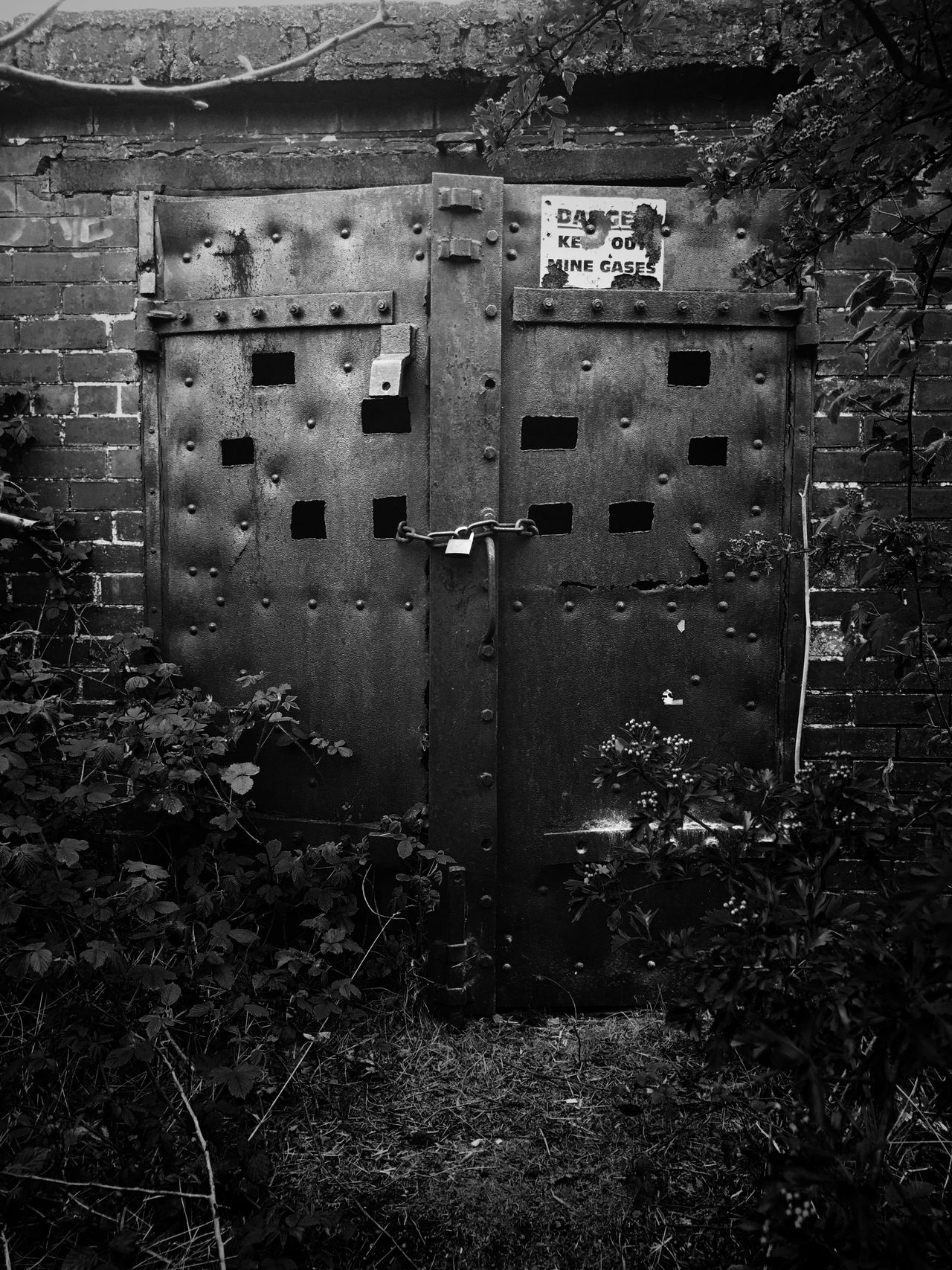 'DANGER. Keep Out. Mine Gases.' Door No People Day Abandoned Outdoors Mine Close-up Architecture Mining Heritage Mining Industry History Black & White Blackandwhite Black And White Brick Building Brick Overgrown The Architect - 2017 EyeEm Awards