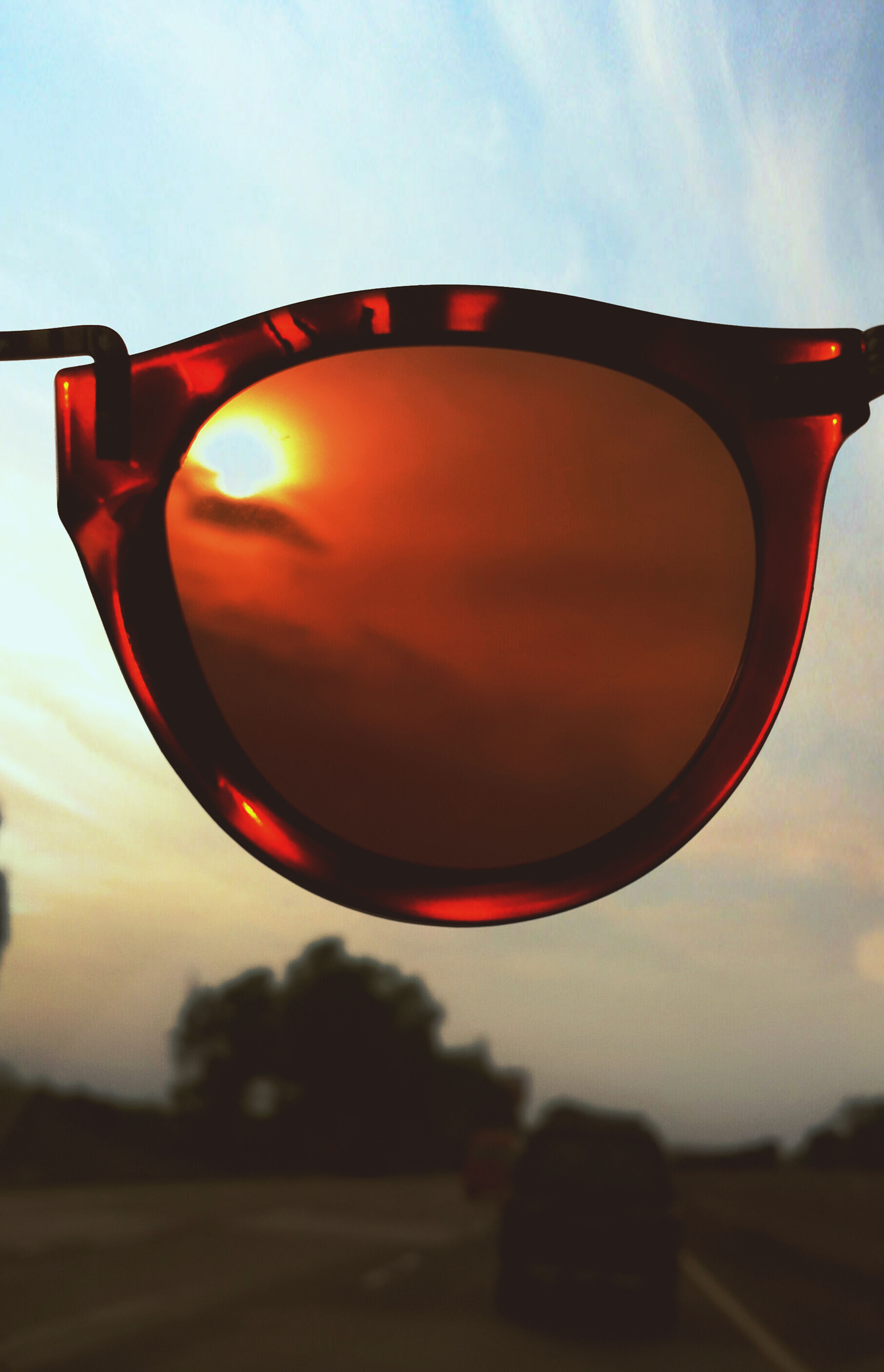 sky, sunset, transportation, close-up, orange color, cloud - sky, reflection, cloud, red, no people, circle, outdoors, nature, sunglasses, focus on foreground, sunlight, sun, part of, dusk, beauty in nature