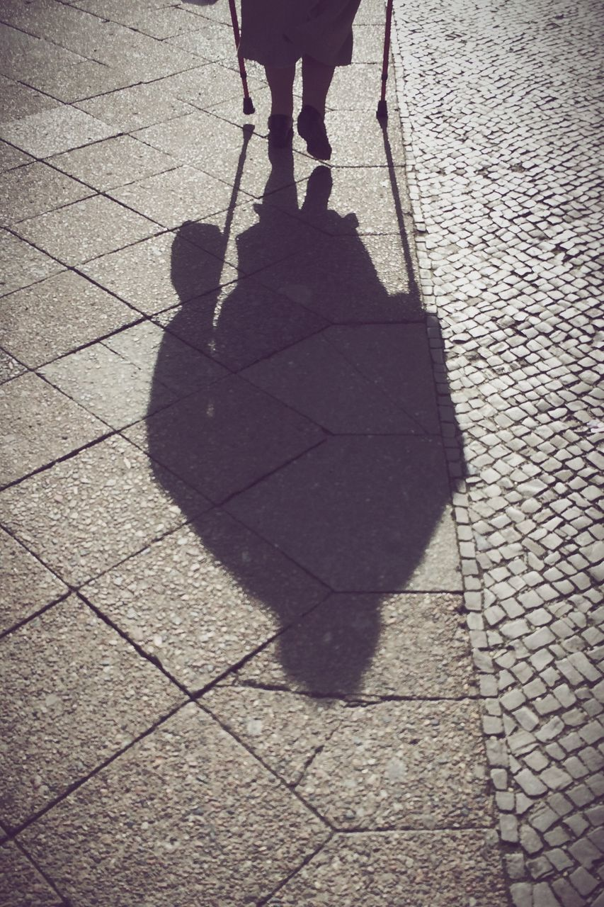 Shadow Of Woman Walking On Footpath