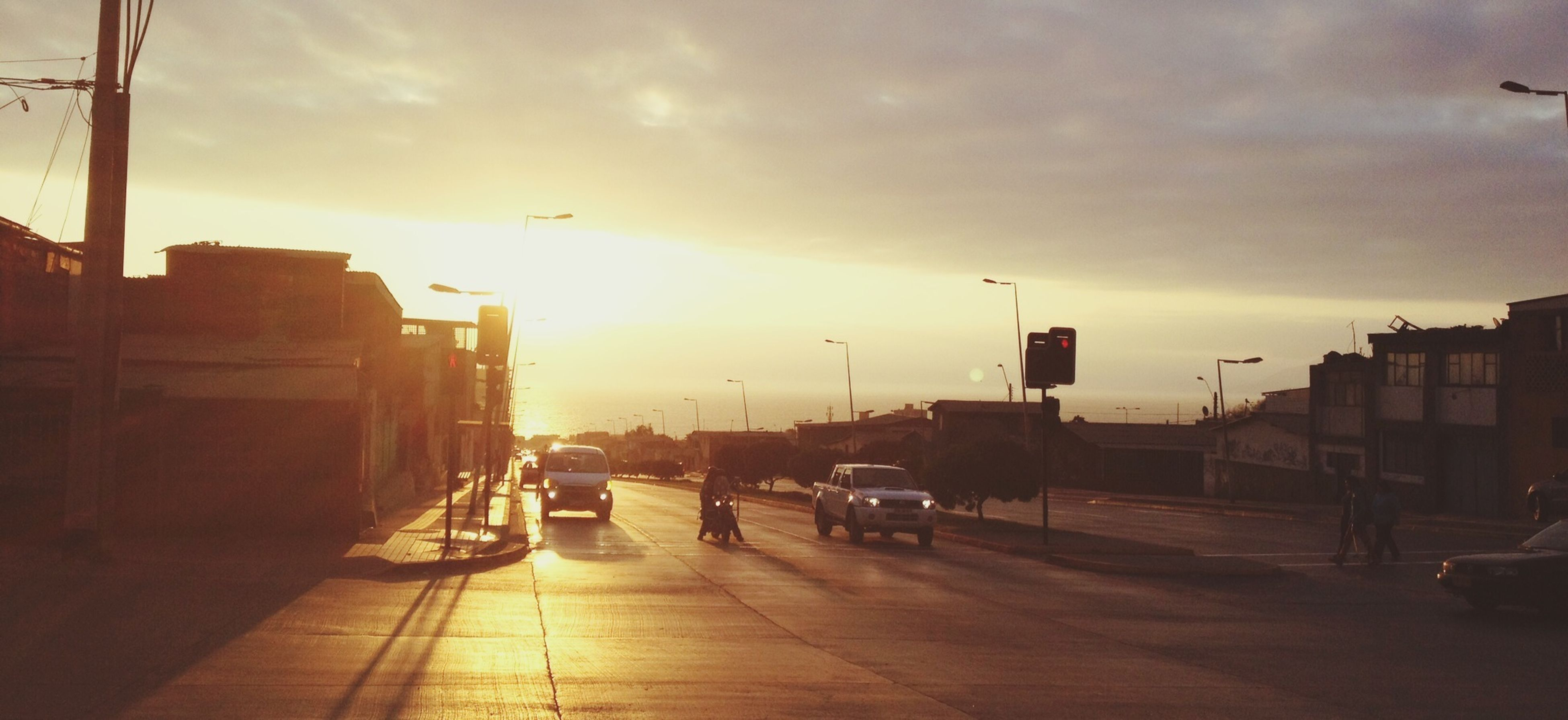 transportation, mode of transport, car, sunset, sky, land vehicle, building exterior, architecture, built structure, city, cloud - sky, street, the way forward, sun, sunlight, road, street light, on the move, incidental people, city life