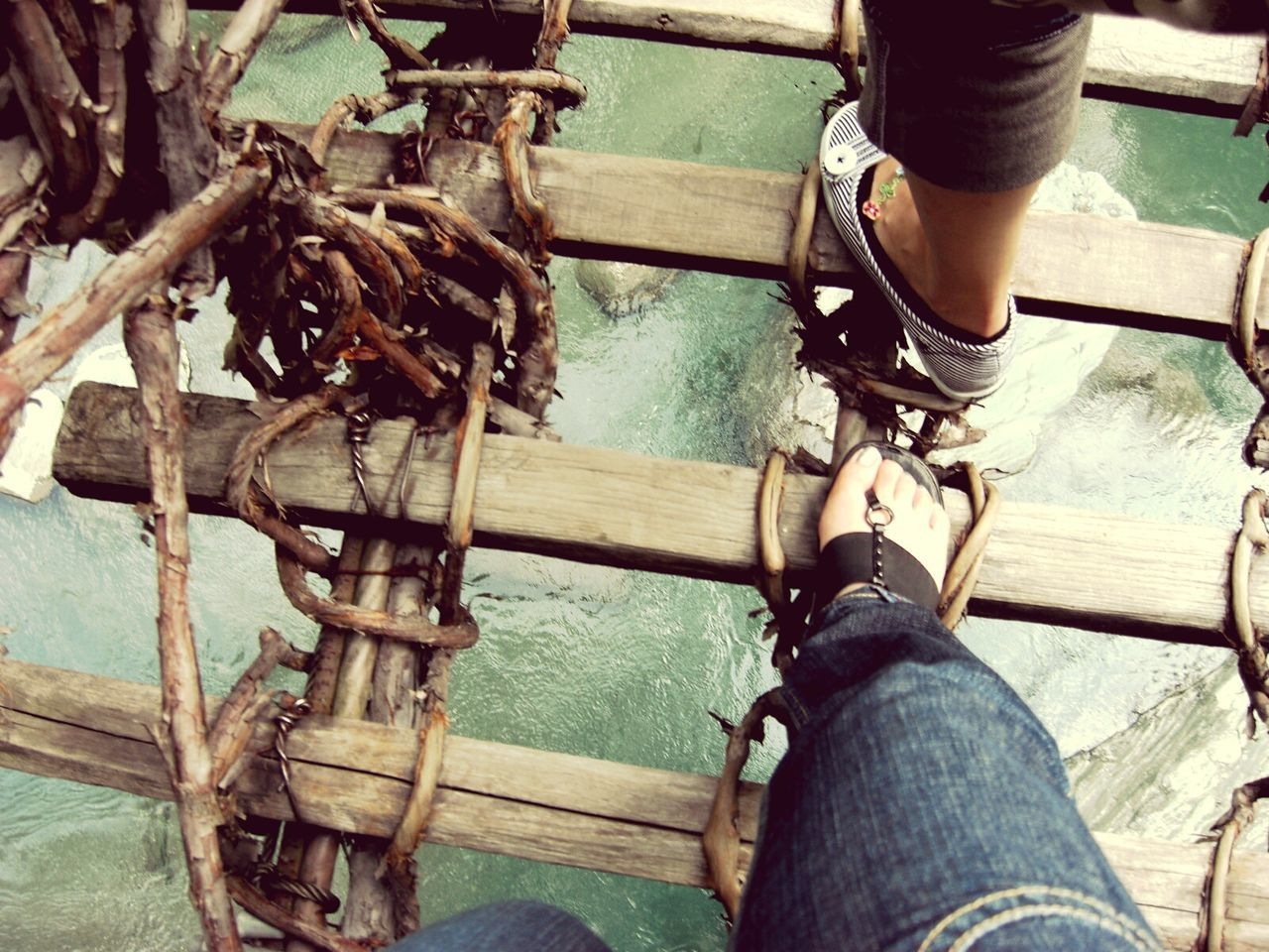 Low Section Of Friends Walking On Footbridge Over River