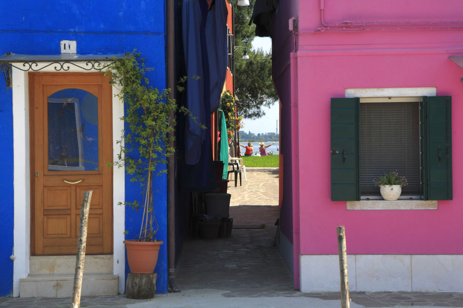 Adapted To The City 2 Women Sitting On The Shore Finger Pointing View Through Buildings Colorful Houses Colorful Home Pink And Blue at Burano Island Venice Architecture Window Door Blue Entrance Outdoors Destinations ıtaly Travel Travel Destinations Blue House Street Photography Urban Exploration Fine Art In And Out Miles Away Minimalist Architecture