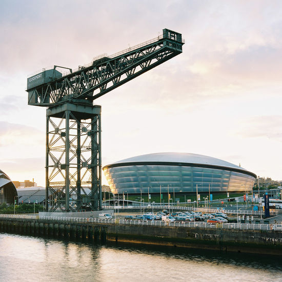 The sun sets on Finnieston Crane and the SSE Hydro at the Scottish Event Campus. Event Finnieston Crane Glasgow  Golden River Clyde Sse Hydro Scotland Scottish Scottish Event Campus Travel Architecture Building Exterior Built Structure Clouds Day Evening Golden Hour Industry No People Outdoors Ship Building Sky Sunset Transportation Water