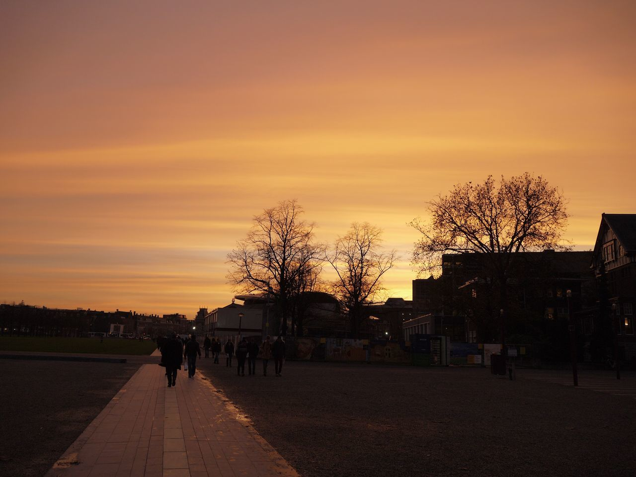 sunset, silhouette, built structure, tree, walking, sky, building exterior, outdoors, architecture, bare tree, road, real people, beauty in nature, nature, city, day